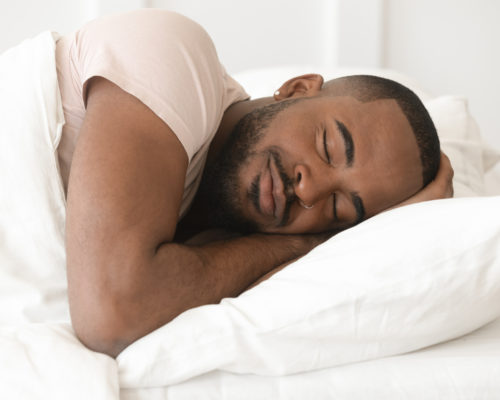 Serene calm handsome young black man sleeping well alone on orthopedic soft pillow under warm duvet, african american guy lying asleep in comfortable cozy bed enjoy good night peaceful healthy sleep
