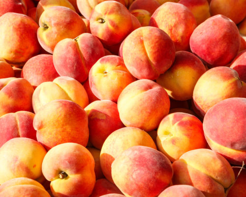 Fresh picked yellow peaches at an outdoor farmer's market