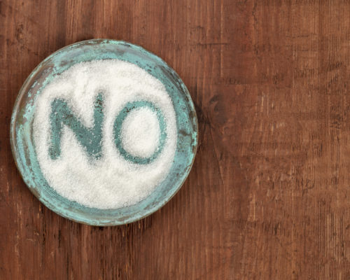 No sugar concept, the word drawn on a plate with sugar, shot from above on a dark rustic background