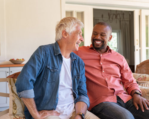 Two friends talking while sitting on couch in the courtyard. Senior man and african guy laughing while in conversation sitting outside home. Two men talking to each other and enjoying.