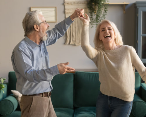 Joyful active old retired romantic couple dancing laughing in living room, happy middle aged wife and elder husband having fun at home, smiling senior family grandparents relaxing bonding together
