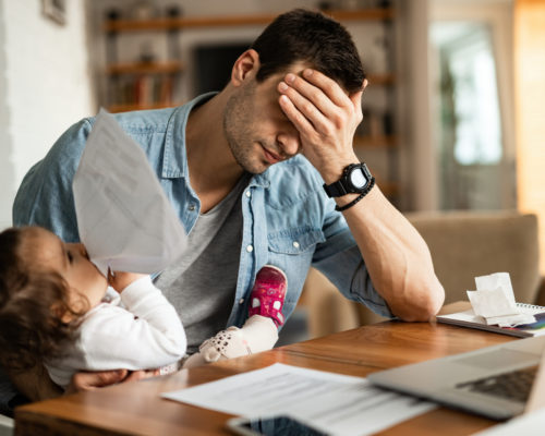 Young father feeling exhausted and having a headache while babysitting his small daughter and working at home.