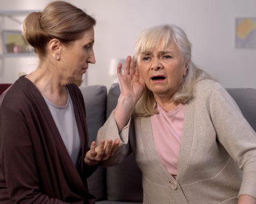 Old deaf woman listening senior friend, hearing disease, old age health care