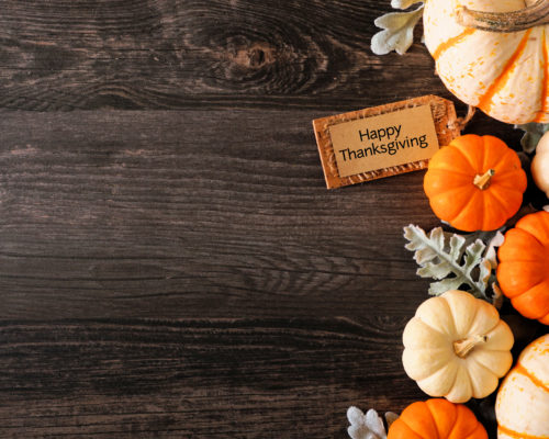 Happy Thanksgiving tag with fall side border of pumpkins and leaves on a dark wood background with copy space