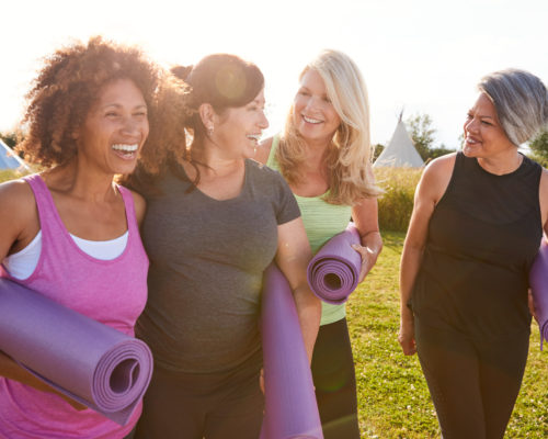 Group Of Mature Female Friends On Outdoor Yoga Retreat Walking Along Path Through Campsite