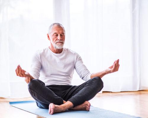 Active senior man meditating at home, eyes closed.