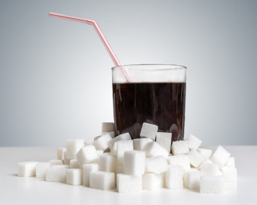 Cola drink in glass and many sugar cubes around. Unhealthy eating concept.