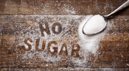 high-angle shot of a wooden table sprinkled with sugar where you can read the text no sugar and a spoon full of sugar