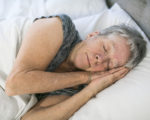A Senior aged woman on bed at home feeling sad