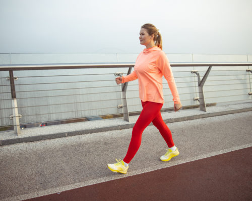 Charming sporty lady having race walking training outdoors stock photo