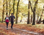 Mature Couple Running Through Autumn Woodland Together