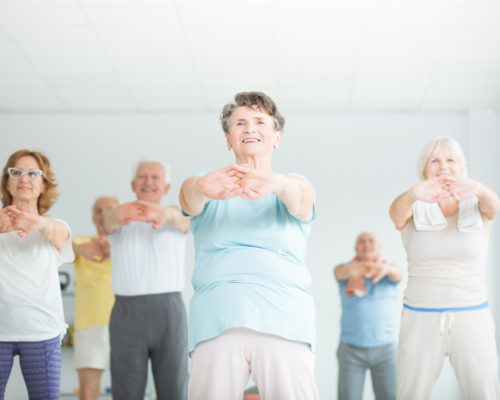 Low angle of group of athletic senior people stretching in fitness studio