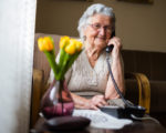 Old woman with gray white hair and glasses sitting in her armchair in her home and talking on the phone. Grandmother is happy to talk to her children and grandchildren.