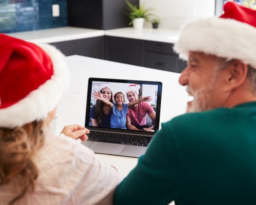 Multi-Generation Hispanic Family Wearing Santa Hats With Laptop Having Video Chat At Christmas