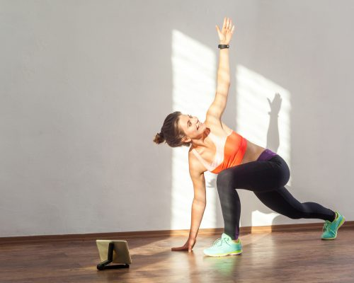 Lunge with spinal twist. Positive fit woman with bun hairstyle and in tight sportswear practicing while watching training video on tablet. indoor studio shot illuminated by sunlight from window