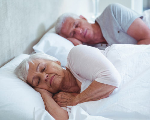 Senior couple sleeping on bed at home