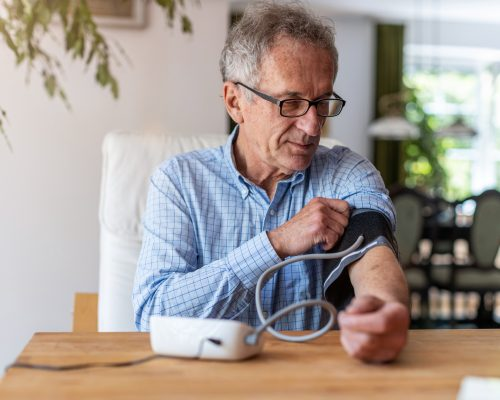Senior man using medical device to measure blood pressure