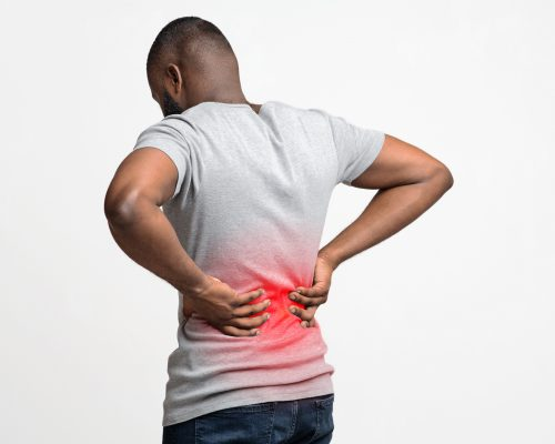 Afro guy holding both hands on lower back, pain in spine, inflamed zone highlighted in red, white background, free space