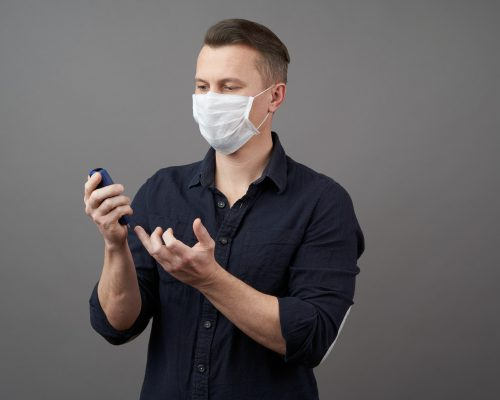 Man checking blood sugar level with glucometer. Young man with medical face mask measuring blood sugar level. Diabetes and Coronavirus (COVID-19). Coronavirus poses greatest risk for diabetes