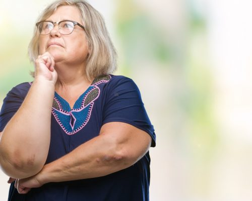 Senior plus size caucasian woman wearing glasses over isolated background with hand on chin thinking about question, pensive expression. Smiling with thoughtful face. Doubt concept.