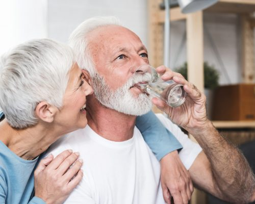 Happy beautiful senior man, white beard and grey hair, holding transparent glass in his hand and drink water. Smiling wife near by. Concept healthy life and diet for senior people. Closeup.