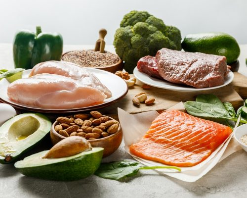 raw salmon, meat and chicken breasts near green vegetables isolated on grey, ketogenic diet menu