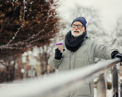 Calm bearded walking alone in the park in winter and holding a carton cup of hot chocolate
