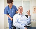 Portrait of a disabled patient screaming to a nurse