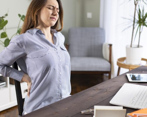 Freelancer young woman suffering with back pain while working in her office at home
