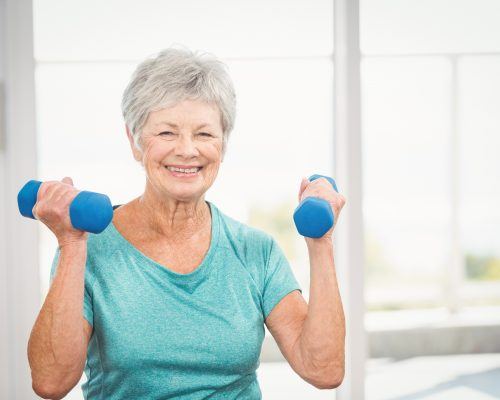 Portrait of happy senior woman holding dumbbell at home