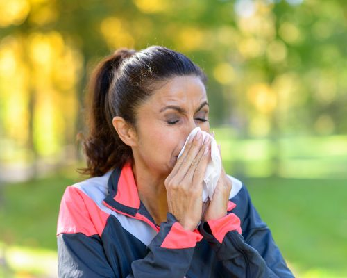 Woman blowing her nose on a tissue outdoors in a leafy green park while out jogging conceptual of seasonal flu or allergies