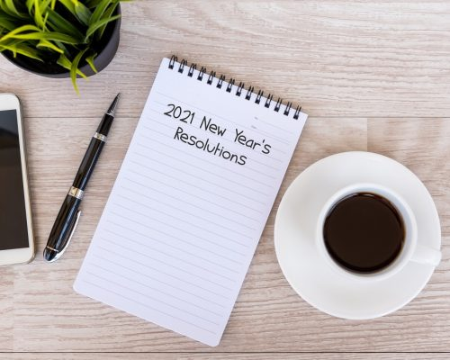 2021 New Year's Resolutions text on note pad with smart phone and cup of coffee