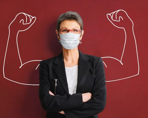 woman in medical face protection mask indoors on blue background