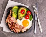 Grilled bacon and avocado, fried eggs with spinach and cherry tomatoes in cast-iron pan. Gray concrete background. Top view. Ketogenic diet. Low carb high fat breakfast. Healthy food concept