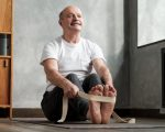 Senior hispanic man sitting in paschimottanasana or Intense Dorsal Stretch pose, seated forward bend posture, exercise for hips and spine at home using belt.