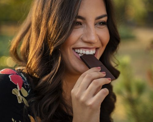 Closeup portrait of charismatic cheerful young woman eating chocolate and smiling