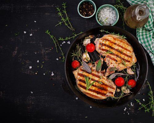 Grilled pork steaks in frying pan on dark background. Top view, overhead, copy space
