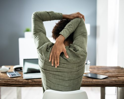 Rear View Of A Businessman Stretching His Arms In Office