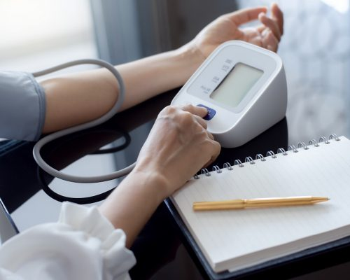 Woman measuring blood pressure by using digital sphygmomanometer with empty white notebook or diary on the desk at home. Medical and healthcare concept.