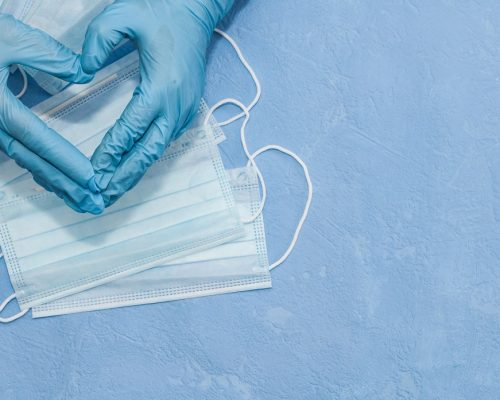 Protective medical white face mask on a blue background. View from above. Virus Prevention Space for text. Close up