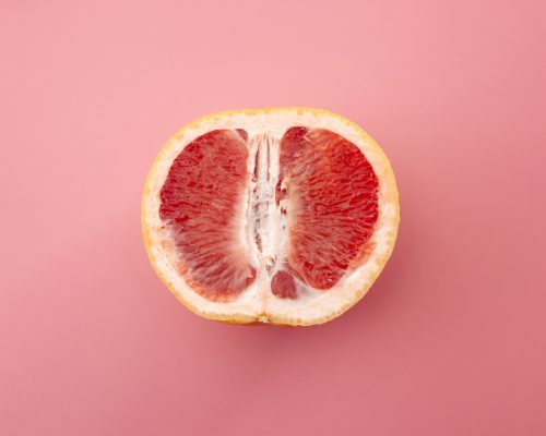 Sexuality, erotic tension and metaphor for female sexual organs concept with grapefruit isolated on pink background