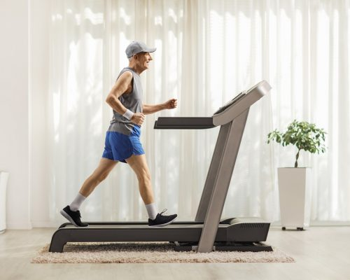 Full length profile shot of an active senior man on a treadmill in a luxurious home