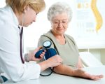 Female doctor measuring blood pressure of senior women