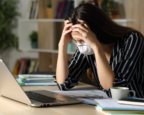 Sad teleworker woman wearing mask with problems due coronavirus sitting on a desk with laptop in the night at home office