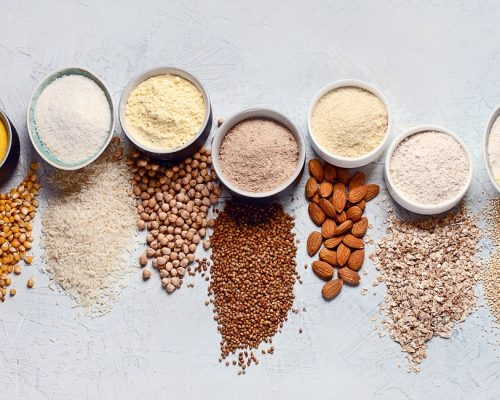 Various gluten free flour - chickpeas, rice, buckwheat, quinoa, almond, corn, oatmeal on grey background.