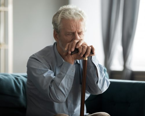 Depressed disabled retired elderly 50s grandfather hold in hands walking stick sit alone on couch looking lonely and unhappy, health problems, physically handicapped person, movement disorder concept