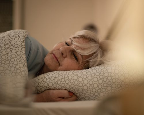 Mature woman lying on the bed and sleeping at night.