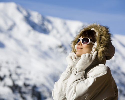 portrait of a woman with sunglasses on a terrace in the snowy mountains