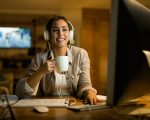 Young smiling woman wearing headphones while using computer and drinking coffee in the evening at home.
