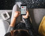 Young woman measures blood pressure sitting on sofa at home with smartphone connected to device - Concept of health, well-being and love for oneself - Millennial in a moment of private life